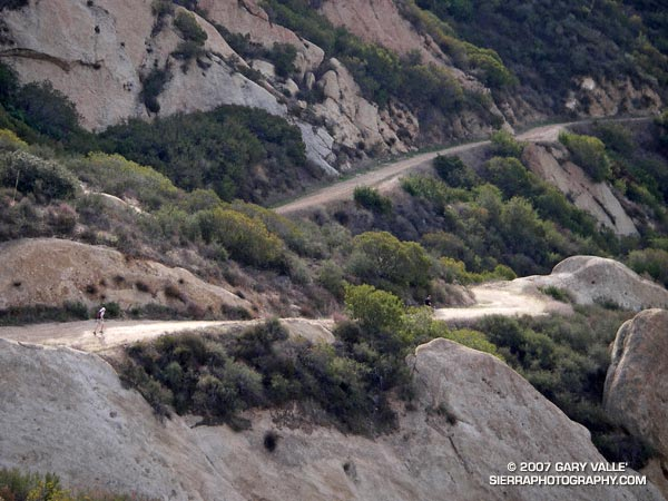 A trail runner cruises down Calabasas Peak Motorway on the way to the Stunt High Trail, Backbone Trail, Saddle Peak, and Tapia Park