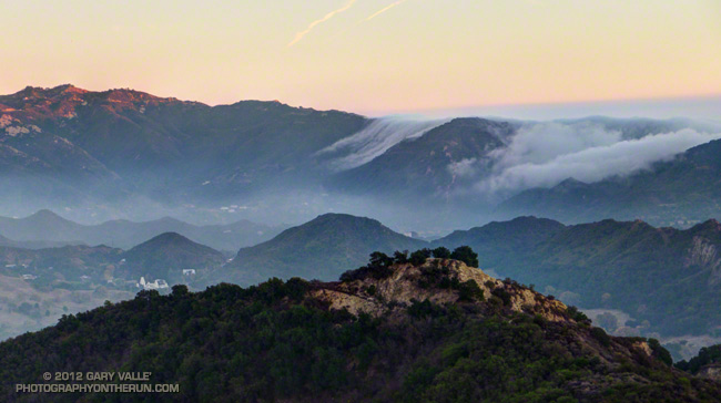 The marine layer spills over the crest of the Santa Monica Mountains