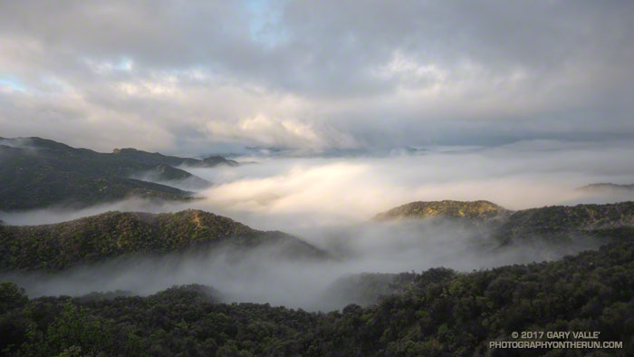 The first rays of sunlight illuminate the ridge tops, fog and clouds in the Santa Monica Mountains.